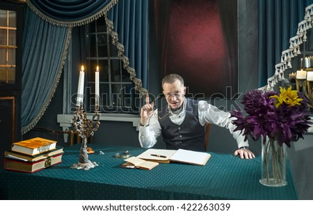 Happy man with eyeglasses in hand at the table in his study
