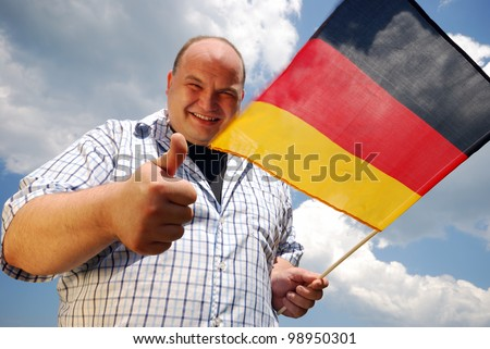 happy man with german flag outdoors in summer - stock photo