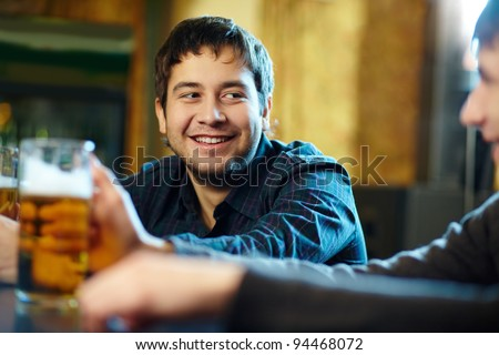 Happy man with glass of beer looking at his friend in pub - stock photo