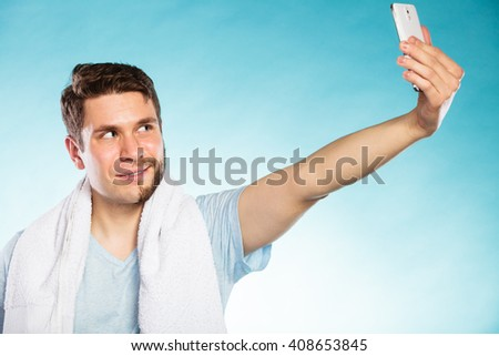 Happy man with half shaved face beard hair taking selfie self photo with smartphone camera. Smiling handsome guy on blue. Skin care and hygiene. - stock photo