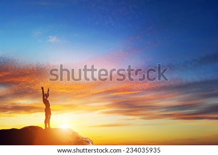 Happy man with hands up standing on the peak of the mountain at lovely sunset. Enjoy life! - stock photo