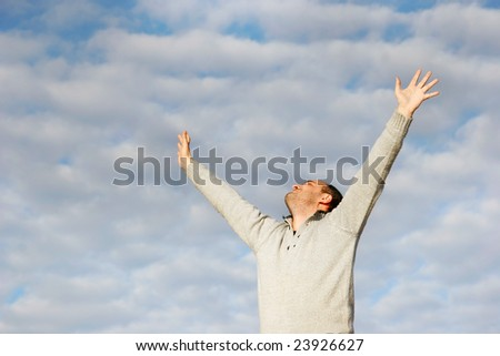 happy man with his hands up on sky background