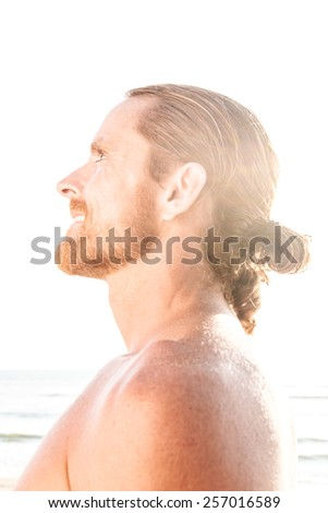 Happy man with his long hair tied in a ponytail enjoying the hot summer sunshine on a tropical beach looking up into the bright flare of the sun with a joyful spiritual smile, profile view - stock photo