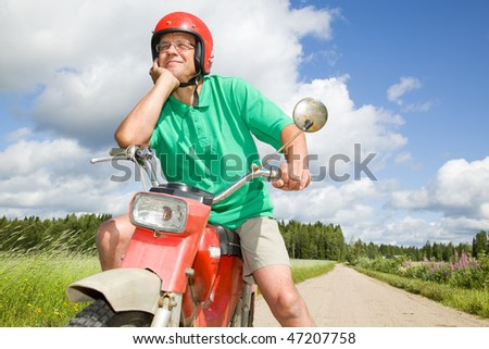 Happy man with his moped - stock photo