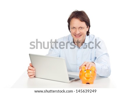 Happy man with laptop and piggy bank - stock photo