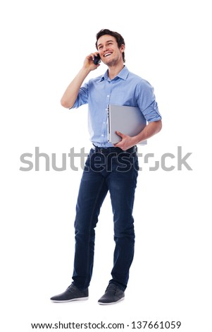 Happy man with laptop talking on the mobile phone - stock photo