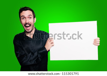 happy man with mustache and black jacket holding blank white board on green background