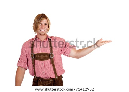 Happy man with oktoberfest leather trousers (lederhose) holds open hand for advertisement. Isolated on white background. - stock photo