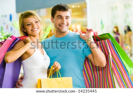 Happy man with paperbags in hand touching his girlfriend while in the shopping mall - stock photo