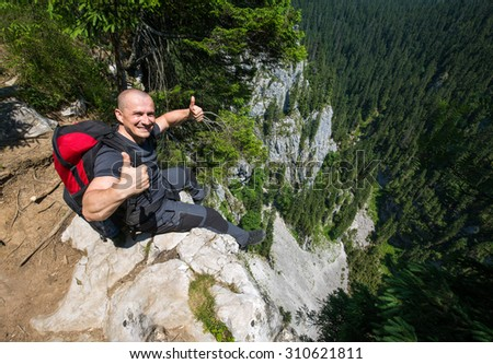 Happy man with thumbs up sitting on the edge of a very high cliff - stock photo