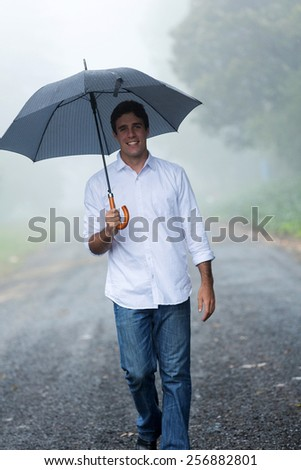 happy man with umbrella walking in the rain - stock photo