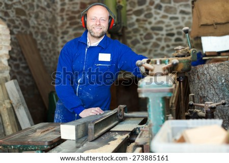 Happy man worker on lathe at  wood workroom - stock photo