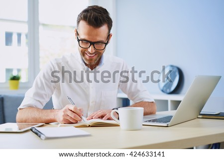 Happy man working from home office doing notes sitting at desk