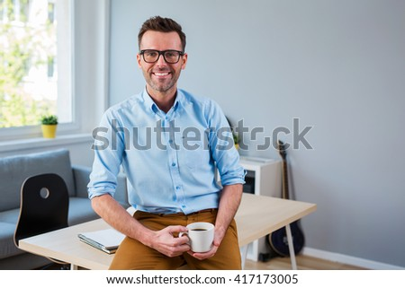 Happy man working from home office standing with coffee