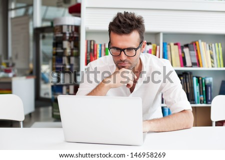 Happy man working on laptop - stock photo