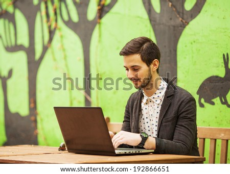 Happy man working on laptop on cafe