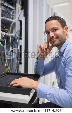 Happy man working with servers in data center - stock photo