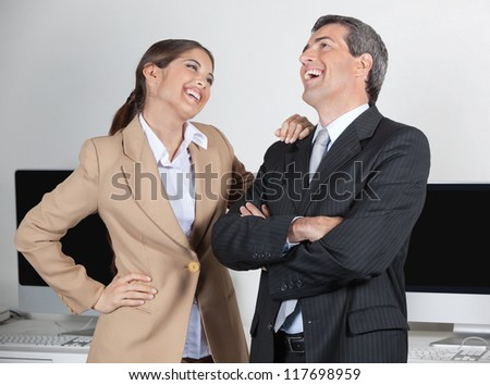 Happy manager and secretary laughing about a joke in the office - stock photo