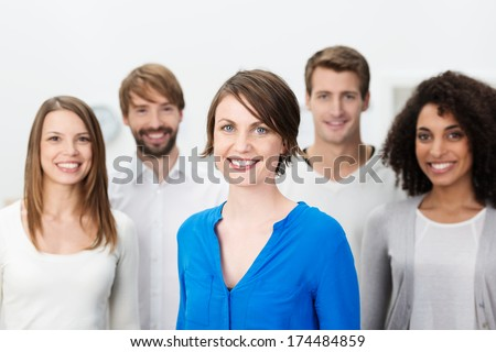 Happy manageress with her business team grouped around her as they look at the camera with friendly smiles - stock photo