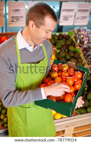 Happy market assistant holding box of tomatoes in the supermarket - stock photo