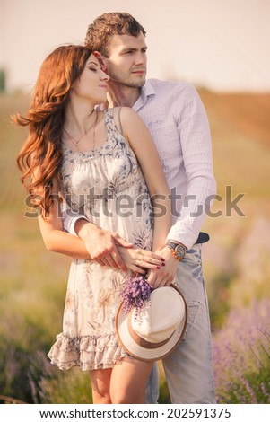 Happy marriage concept. Portrait of a beautiful kissing couple of hipsters in trendy clothing. Outdoor shot. Happy couple having great time together - photographed at sunset against sun - stock photo