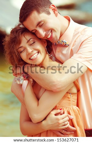 Happy marriage concept. Portrait of a beautiful laughing (smiling) couple of hipsters in trendy clothing. Wedding day. Close up. Outdoor shot - stock photo