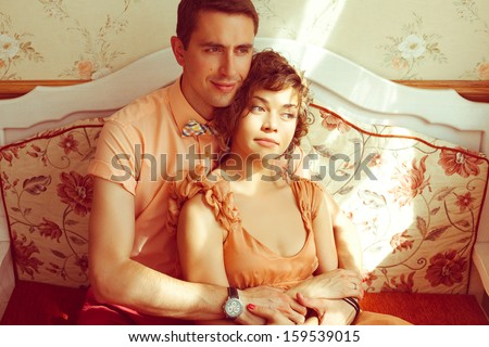 Happy marriage concept. Portrait of a beautiful married couple of hipsters in trendy clothing sitting on the sofa in vintage cafe. Wedding day. Sunlight. Indoor shot