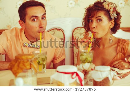 Happy marriage concept. Portrait of a beautiful married couple of hipsters in trendy clothing drinking mojito and having fun in vintage cafe. Wedding day. Hipster style. Close up. Indoor shot