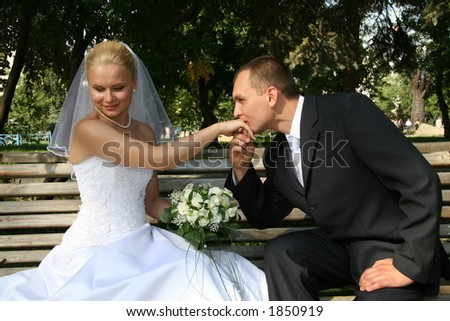 Happy married. Bridegroom kisses bride a hand. This photo is not correction. - stock photo