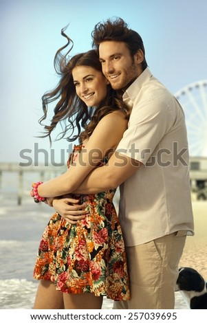 Happy married casual caucasian couple on honeymoon trip standing and embracing at summer holiday beach. Smiling, looking in the distance. - stock photo