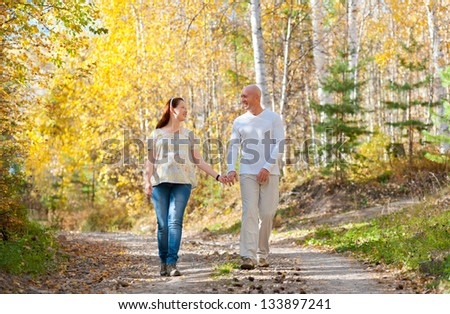 happy married couple - husband and his pregnant wife walk in autumn forest - stock photo