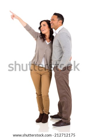 happy married couple pointing on white background - stock photo