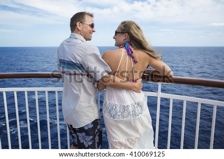 Happy married couple smiling on the balcony of their cruise ship while on vacation together - stock photo