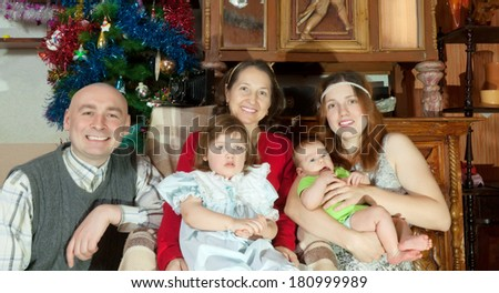 happy married couple with baby girls visiting grandmother for Christmas vacation