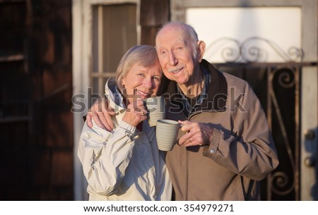 Happy married couple with cups standing outdoors - stock photo