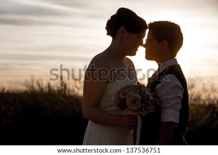 Happy married homosexual couple outdoors at sunrise - stock photo