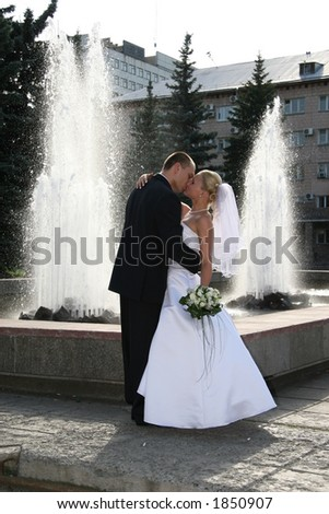 Happy married. The Newlywedses on walk beside fountain. This photo is not correction. - stock photo