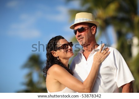 Happy mature adult couple enjoying vacation at tropical resort. Close-up, shallow DOF. - stock photo