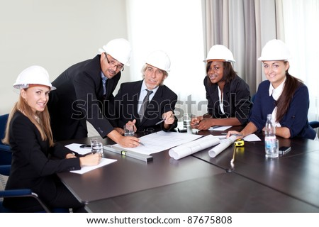 Happy mature architects in a meeting at the office - Looking at the camera and smiling - stock photo