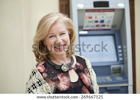 Happy Mature blonde woman near automated teller machine in shop - stock photo
