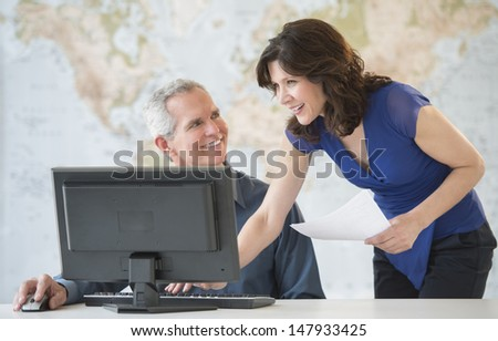 Happy mature business colleagues discussing at office desk with world map in background - stock photo