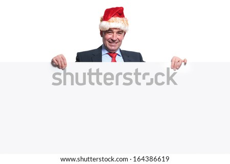 happy mature business man with santa hat  holding a big blank board on white background