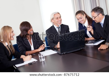 Happy mature business manager discussing targets on his laptop with his team - stock photo