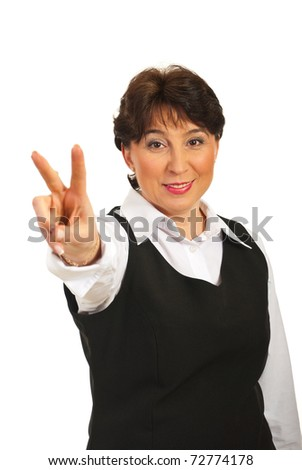 Happy mature business woman showing victory sign hand gesture over white background - stock photo