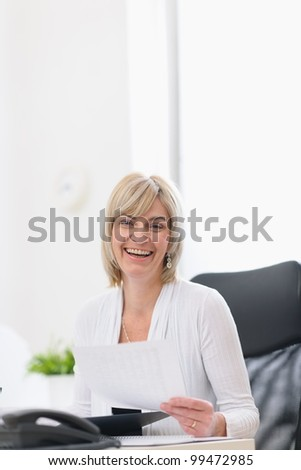 Happy mature business woman working at office