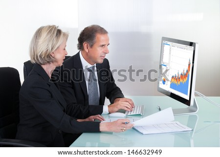 Happy Mature Businessman And Businesswoman Looking At Graph On Computer