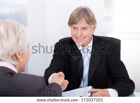 Happy Mature Businessman And Businesswoman Shaking Hands In Office