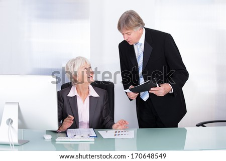 Happy Mature Businessman And Businesswoman Working In Office
