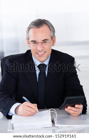 Happy Mature Businessman Calculating Finance With Calculator At Desk