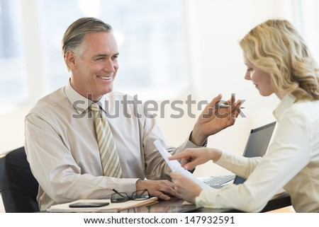 Happy mature businessman discussing with female colleague in office - stock photo